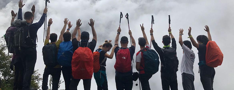 grupo de trekkers saludan a las montañas