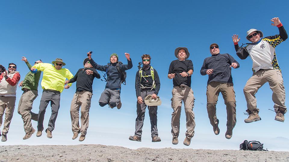 Grupo de trekkers saltan de alegría en el camino a la cima del Kilimanjaro