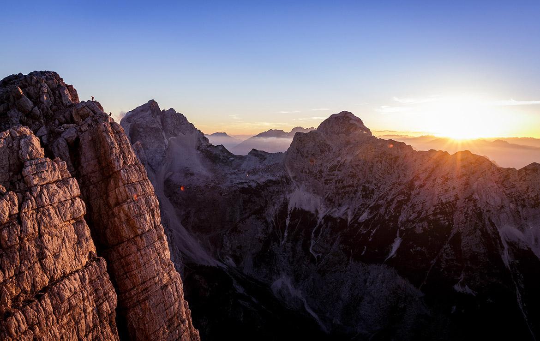 dos personas escalan una pared de los alpes julianos con la puesta de sol de fondo