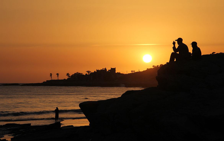 dos hombres ven la puesta de sol en la playa en marruecos