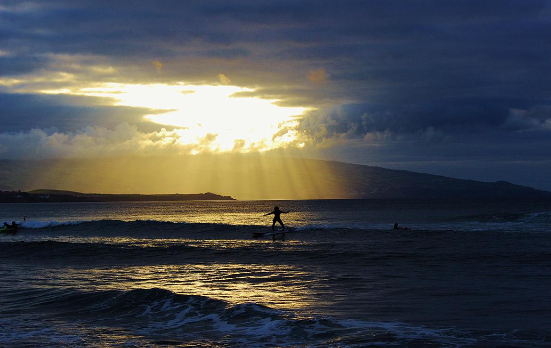El sol del atardecer se filtra entre las nubes sobre unos surferos en las islas azores