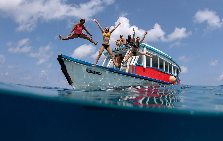 Varias personas saltan desde un barco dhoni