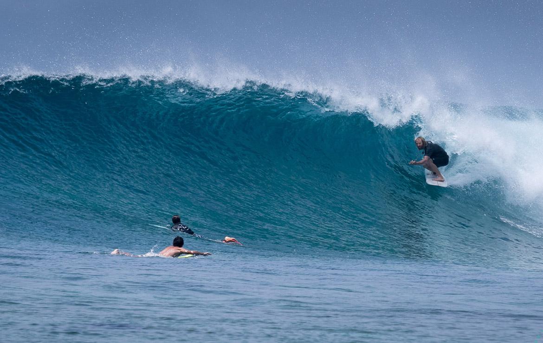 Surfero en una ola de dos metros que empieza a hacer tubo mientras otros reman hacia el pico
