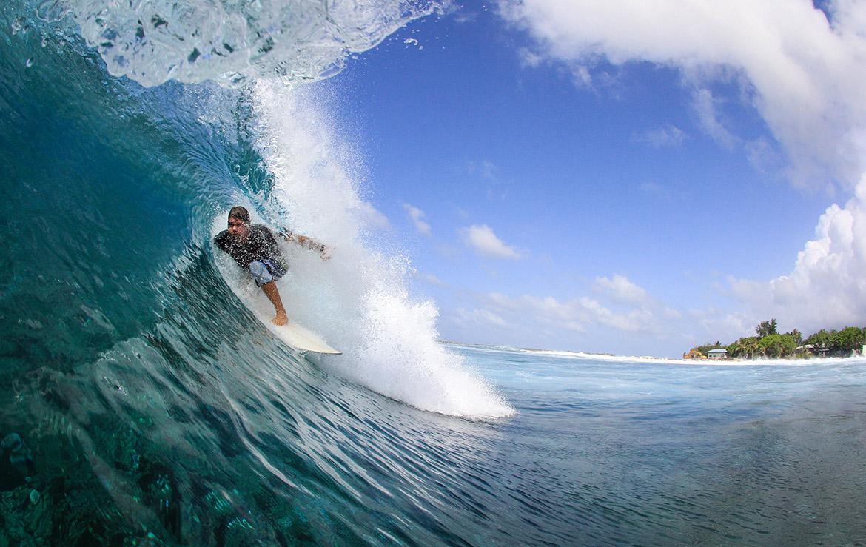 Surfero cogiendo una ola, metido en el tubo con la isla al fondo