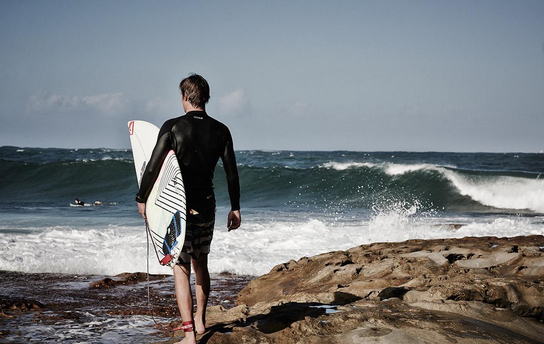 Surfero a punto de entrar al agua desde un Point break en marruecos