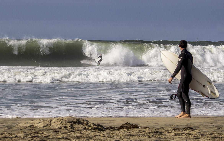 Un surfero mira a otro desde la orilla