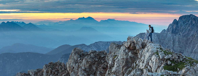Chica contempla la puesta de sol desde una cima de los Alpes Julianos