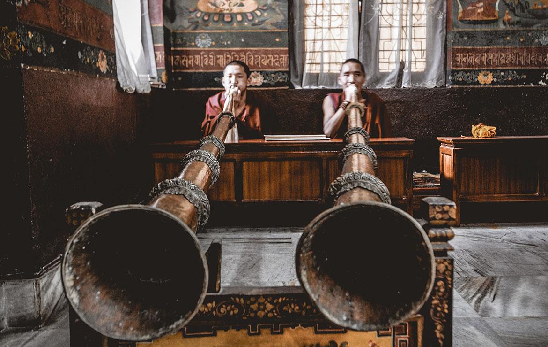 Dos monjes tocan Dungchens en un lamasterio