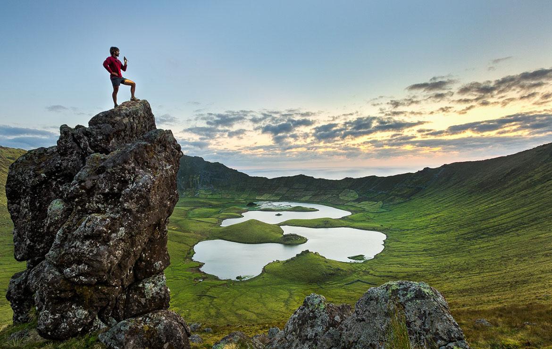 Senderista descansa sobre una roca con un cráter de las azores a su pies