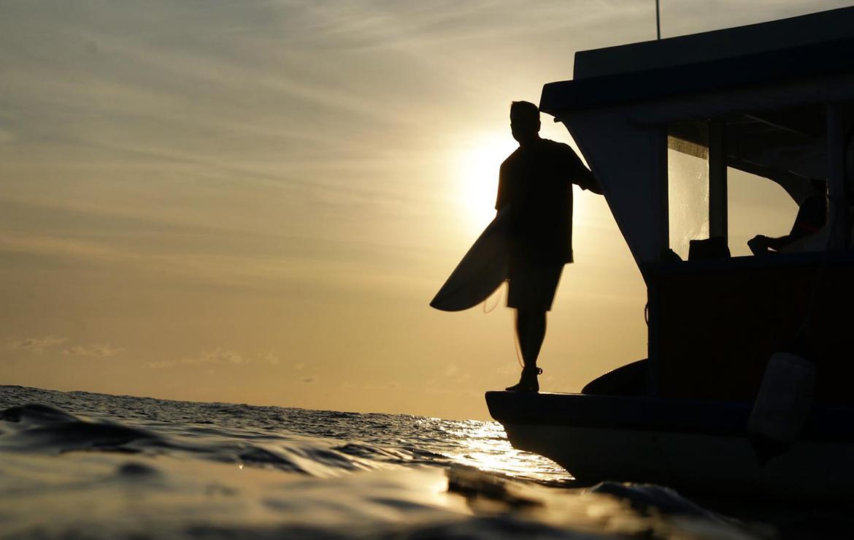 surfer espera el momento para saltar al agua desde un barco en maldivas