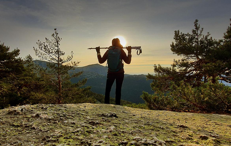 una chica contempla la salida del sol desde una montaña en madrid