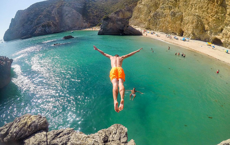 Un chico salta desde una roca al mar