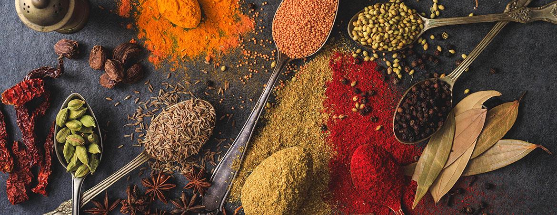 Mesa dispuesta con especias diferentes entre ellas curry