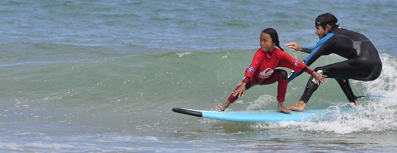 instructor de surf surfea una ola con una niña en la tabla de surf