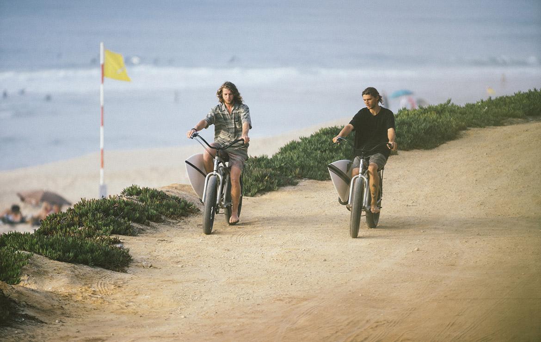 Dos surferos en bici buscan la ola en un surfcamp en Portugal