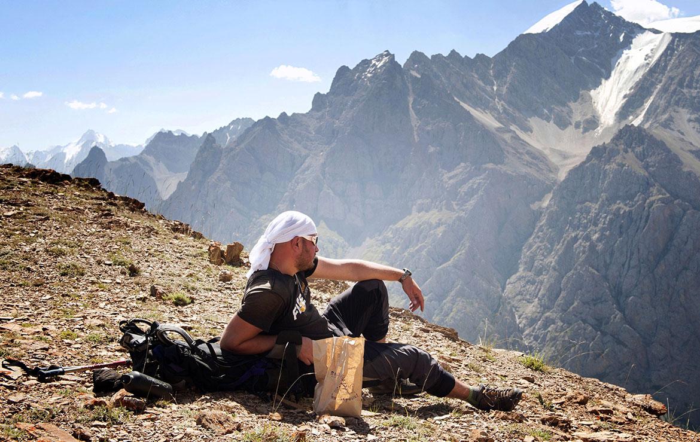 trekker descansa en una cumbre durante un trekking en Kirguistán