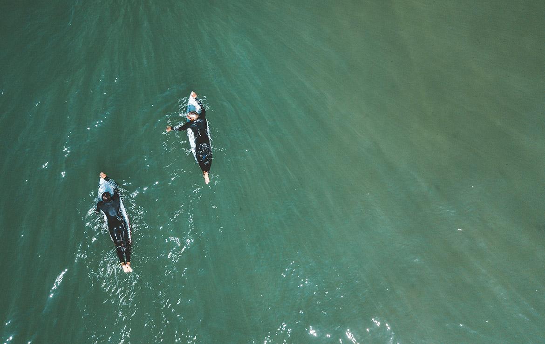 dos surferos reman hacia el pico en la playa de Santa Cruz de noah surfhouse