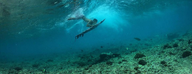 Chica haciendo un pato con una tabla de surf en Maldivas